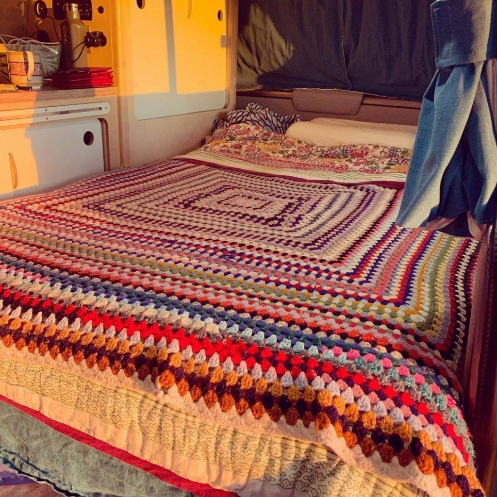 Cosy campervan interior with crocheted blanket